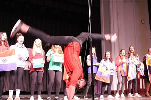 student performs a back walkover on stage
