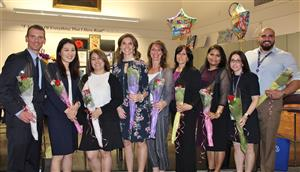 Nine teachers pose with flowers after tenure ceremony