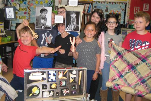 third graders with red trunk of artifacts