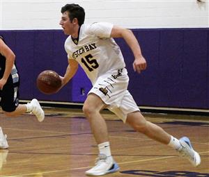 Senior Anthony Reilly dribbles a basketball during a boys' varsity basketball game