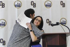 student hugs teacher after receiving award