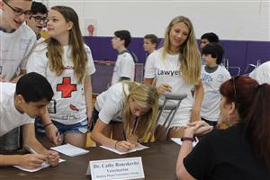 students listen to a veterinarian at career day