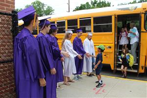 Seniors greet TR students at bus dressed in cap and gown