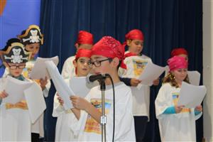 student reads his part at Readers' Theater
