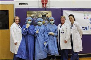 students dressed in scrubs pose with Northwell Health nurses