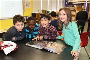 fourth graders look over history books on the Revolutionary War