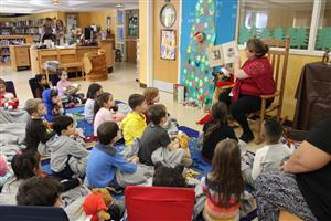 Roosevelt students with blankets and stuffed animals listen to stories in the library