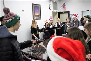 chamber singers caroling in principal's office