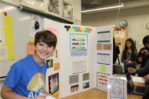 Sixth grade students stands next to his project on creating original tessellation-based artwork