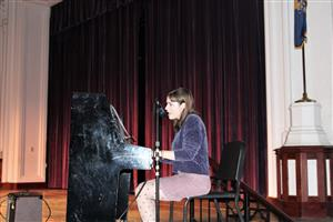 A student plays the piano and sings at International Night