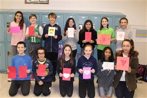 Students hold up valentines cards they made for veterans