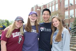 Students smile wearing their college shirts