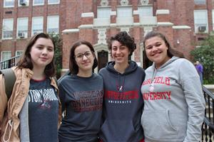 four girls in college shirts