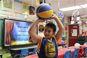 3rd grader portrays a basektball player in the interactive wax museum