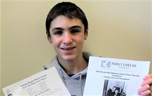 NJHS eighth grader holds up flyers about the fundraiser he is leading for the Family Lives On Foundation