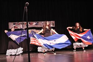 Students dance with flags at International Night