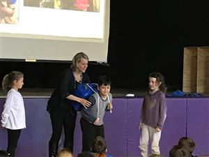 Author Christine Ieronimo demonstrates with students what it is like to carry a water jug in Africa