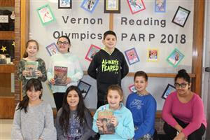 Students pose with books for the Pick a Reading Partner campaign