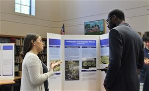 science research student explains her project at symposium