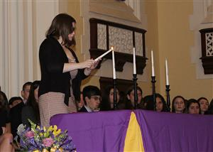 NHS president lights a candle during ceremony