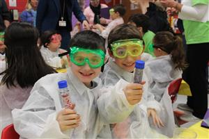 Roosevelt second graders hold up bubbling test tubes after a science activity
