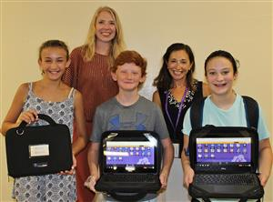 students with Chromebooks pose with administrators