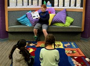 a sixth grader reads a picture book he authored to third graders