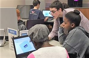 coding club member helps student on computer during Techathon